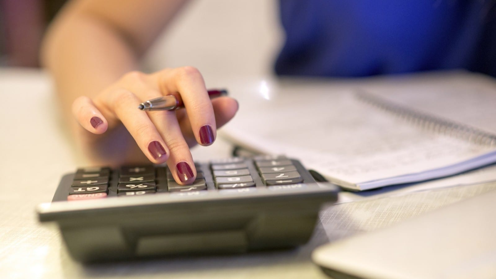 Woman With Calculator Stock Photo