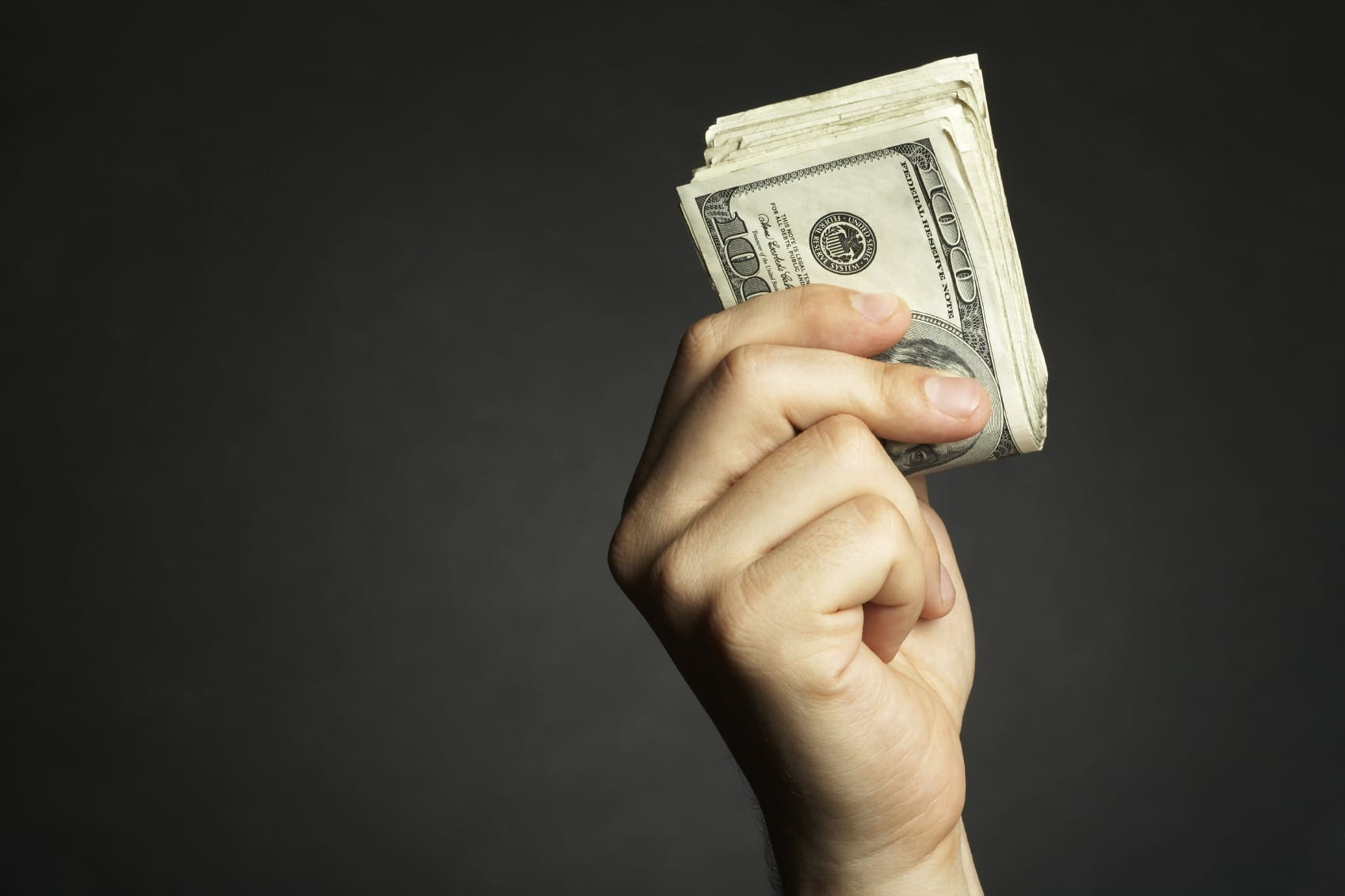 Hand Holding A Large Stack Of Money Stock Photo