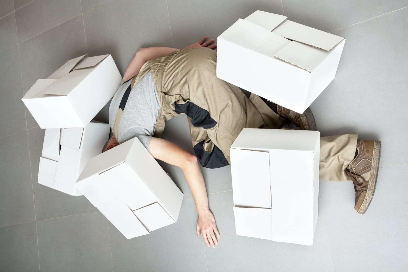 Man Laying Under Boxes Stock Photo