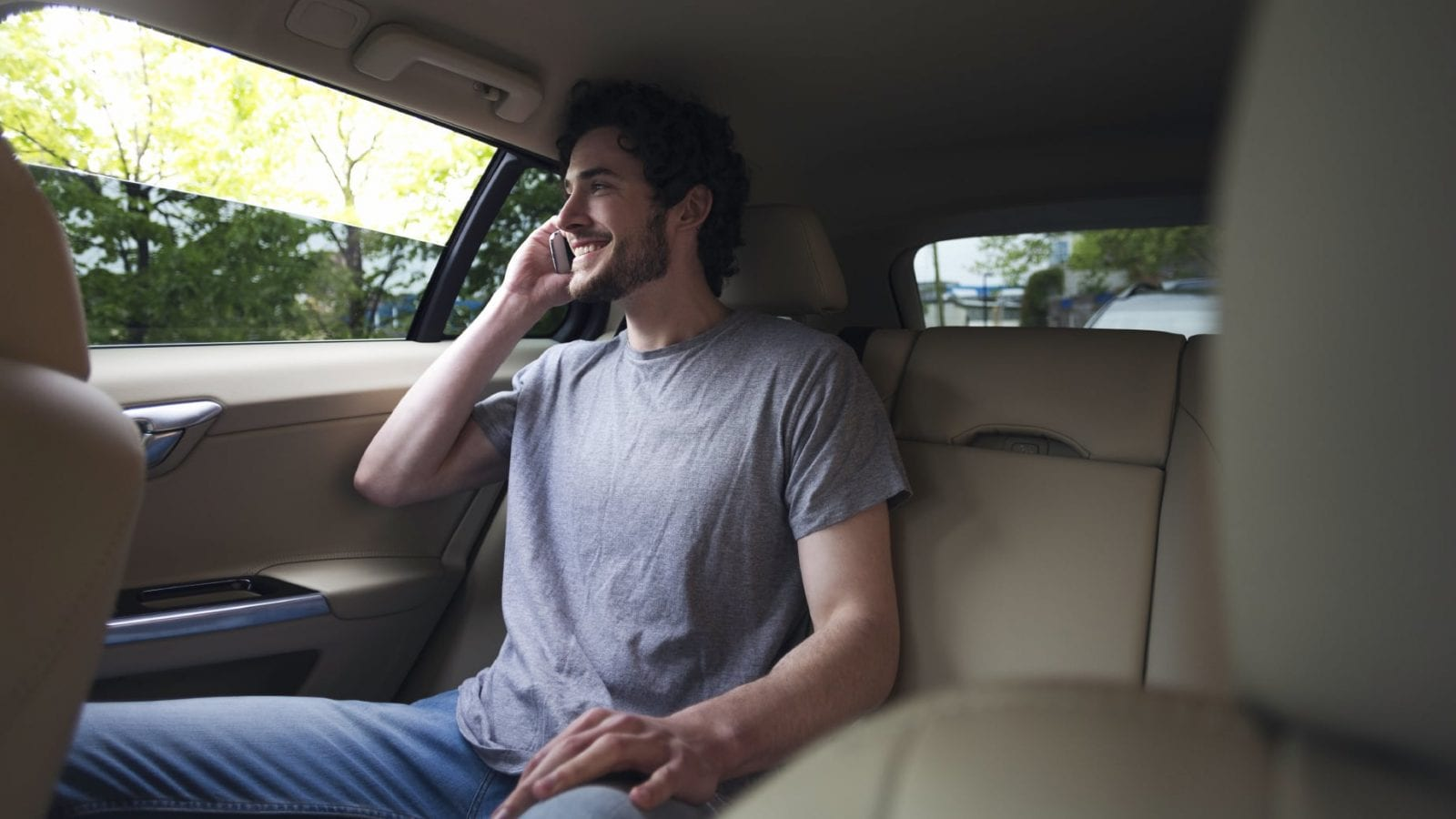 Man Talking On Cell Phone In Back Of Car
