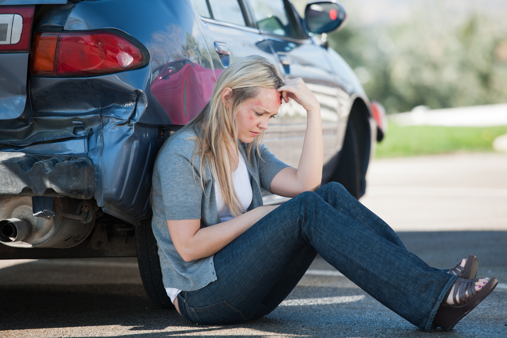 A woman leaning against her car after an accident in Odessa, TX.